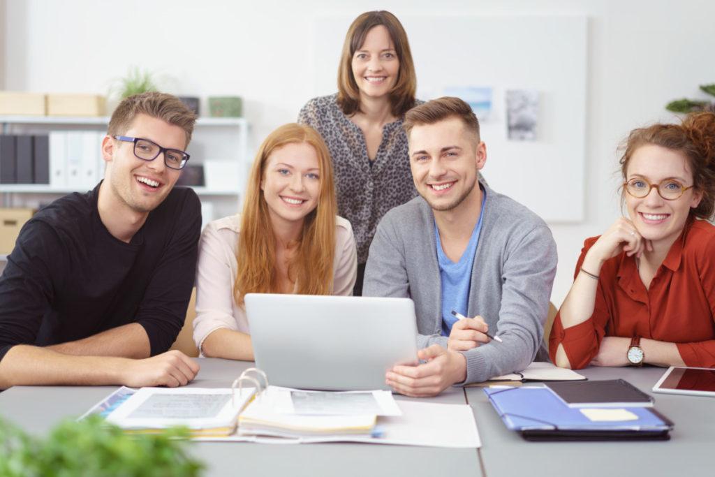 Leute sitzen zusammen und lernen mit laptop und unterlagen